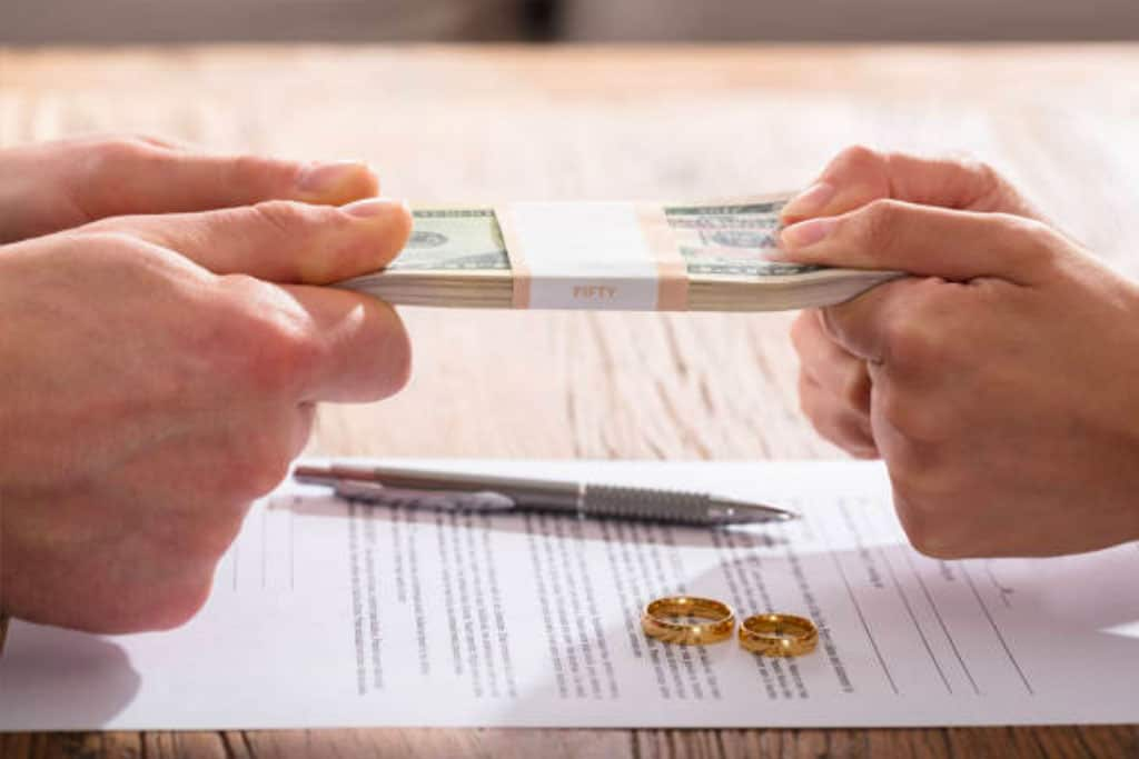 a couple's hands holding a bunch of cash with a separation agreement and rings on the table
