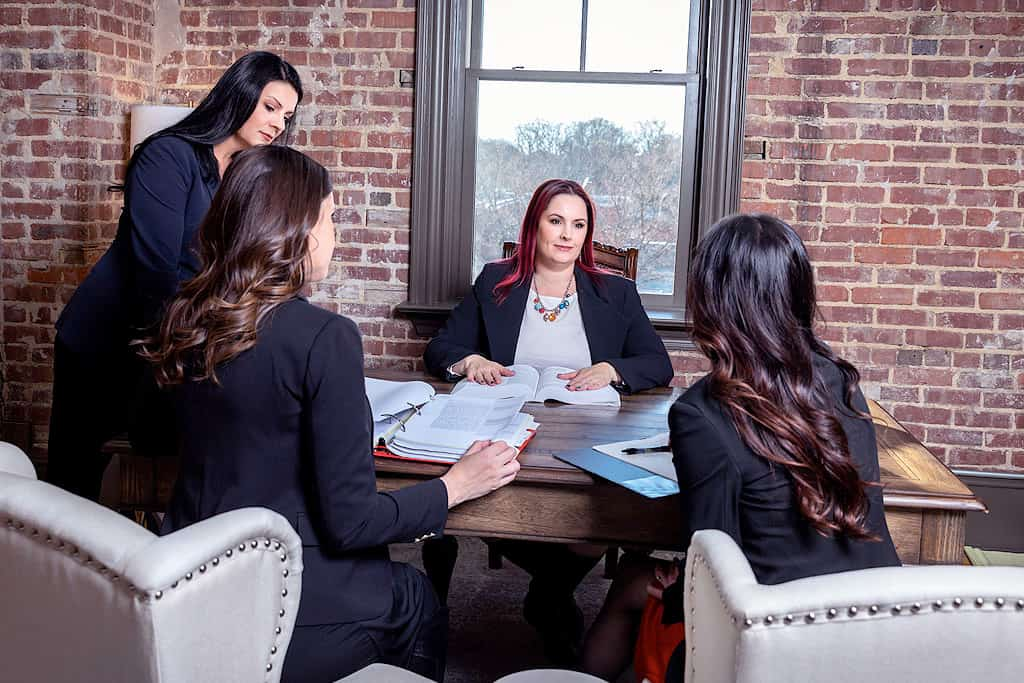Four female attorneys sitting around a table discussing adoption law