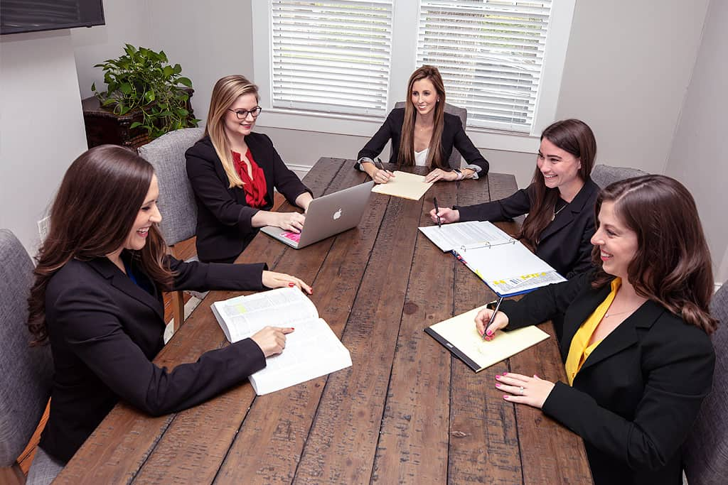 Five female attorneys sitting around the table, smiling, and discussing the case