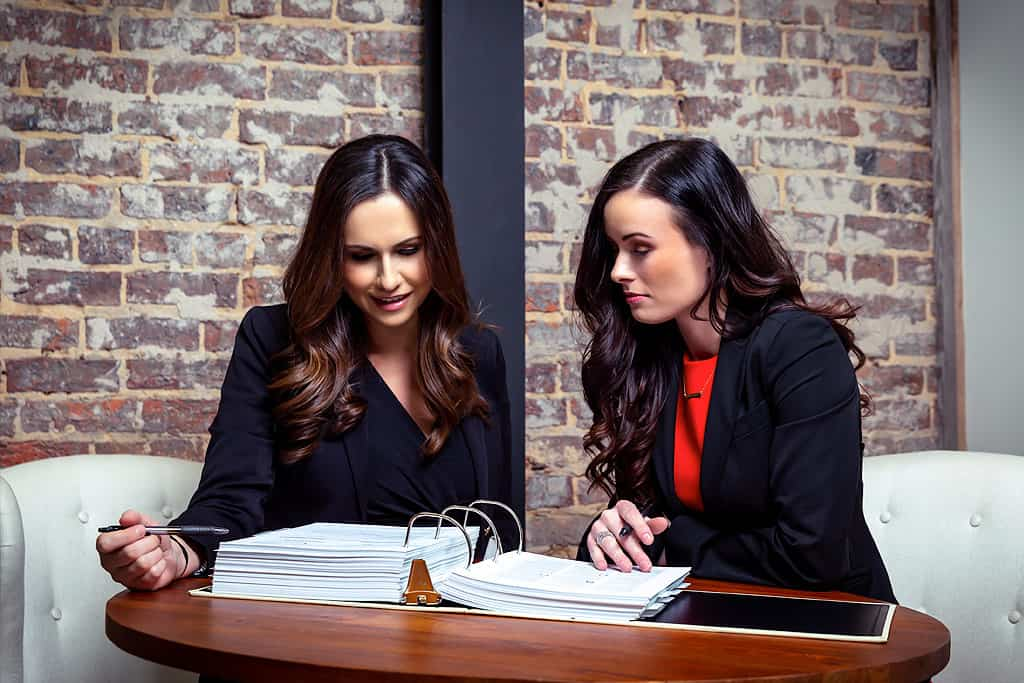 Two female divorce law attorneys looking down on a big book of divorce law