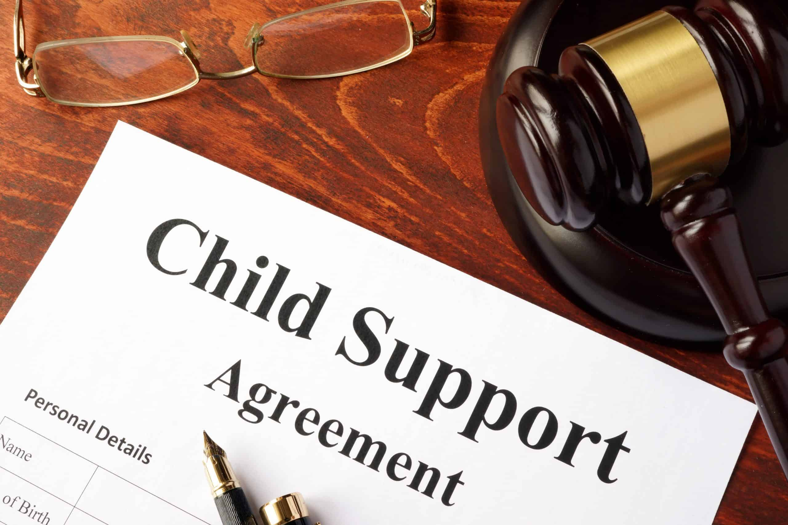 Child Support Agreement with a gavel and glasses on a table