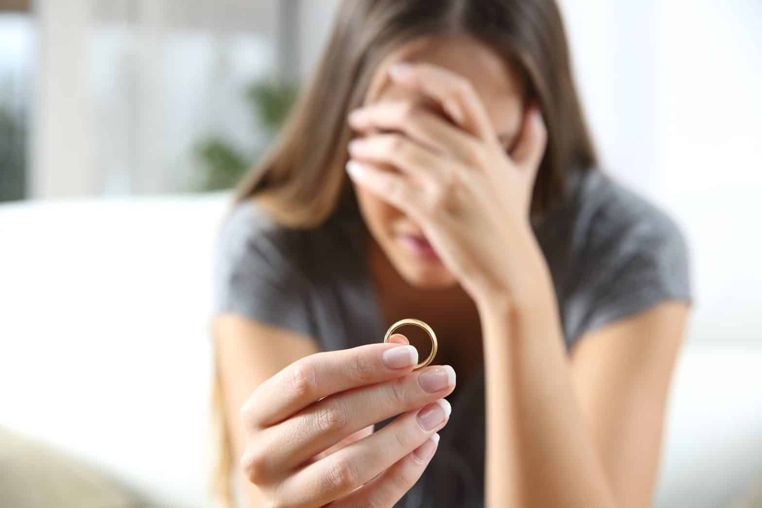 Closeup of a sad woman holding out a wedding ring with her hand covering her face looking sad.