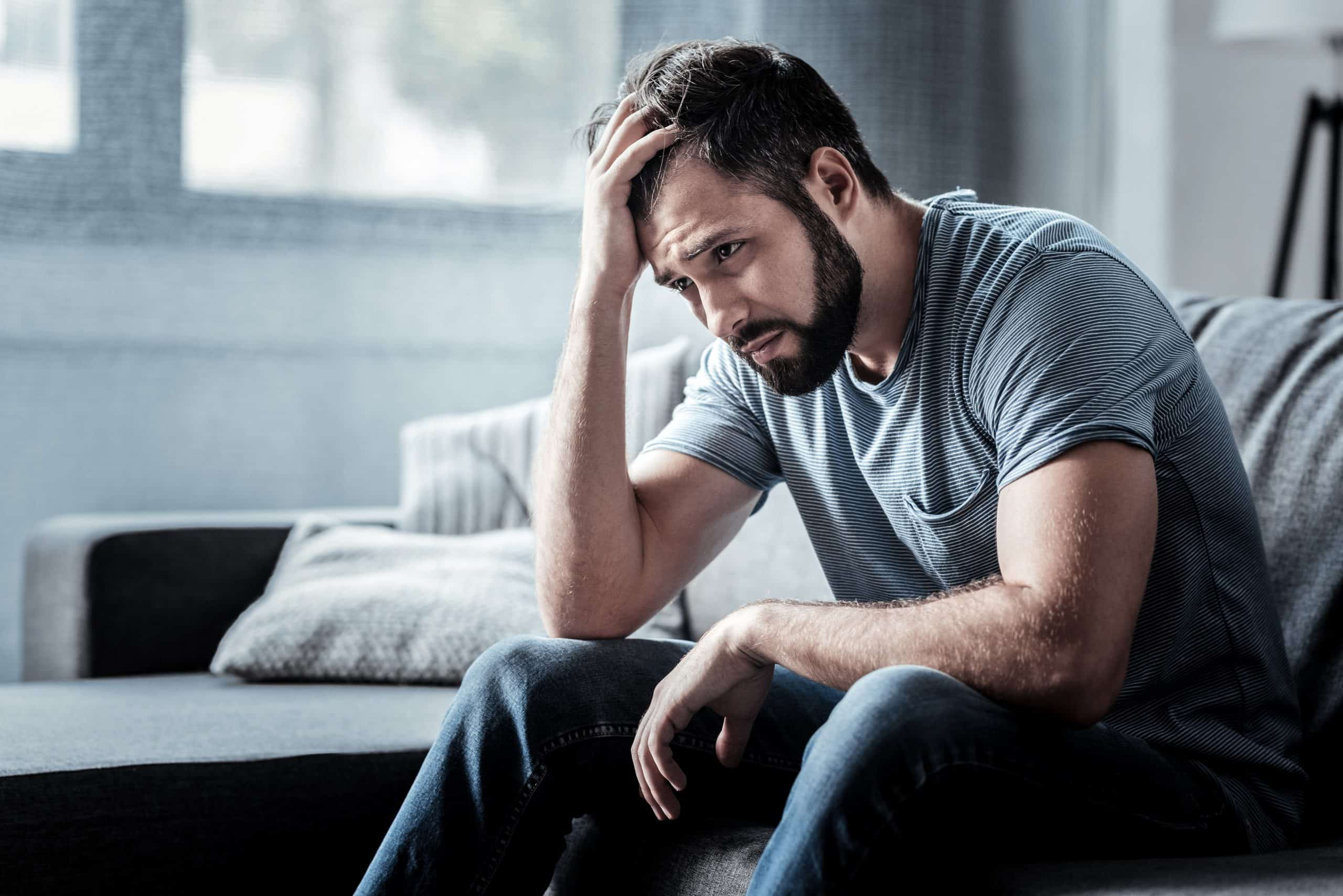 Sad unhappy man sitting on the sofa and holding his forehead