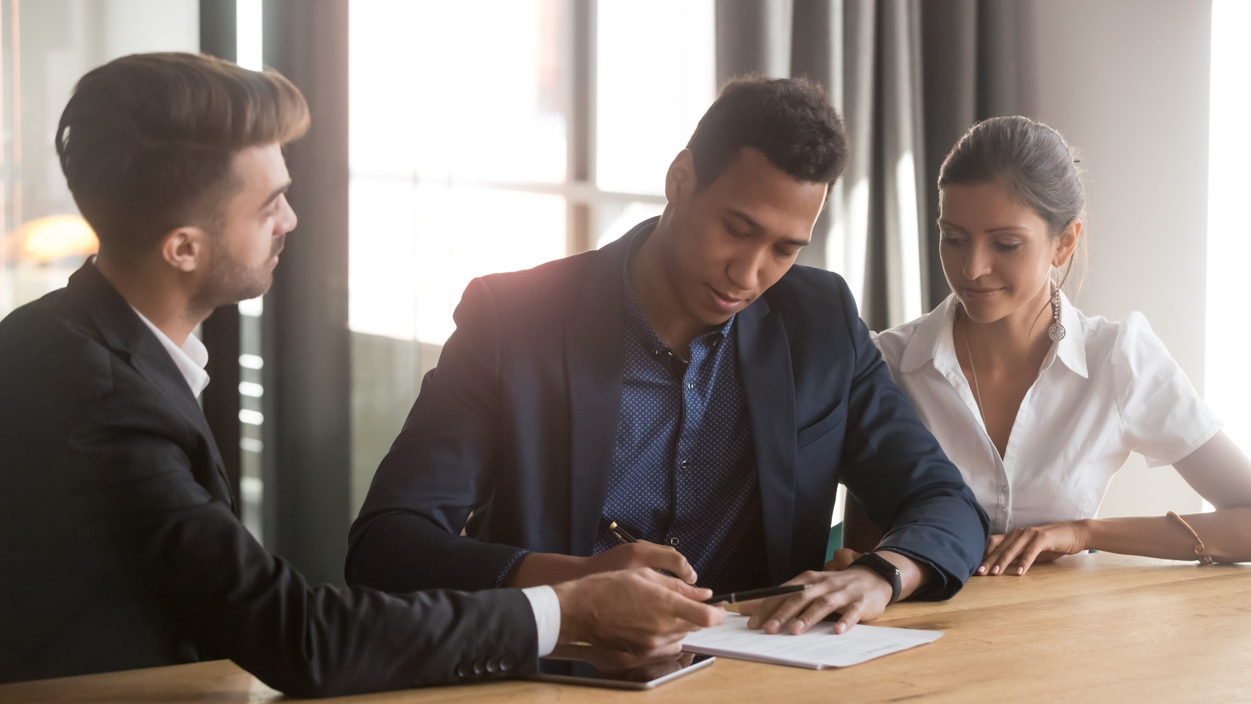 Young, well dressed mixed race couple signing a document together with an attorney