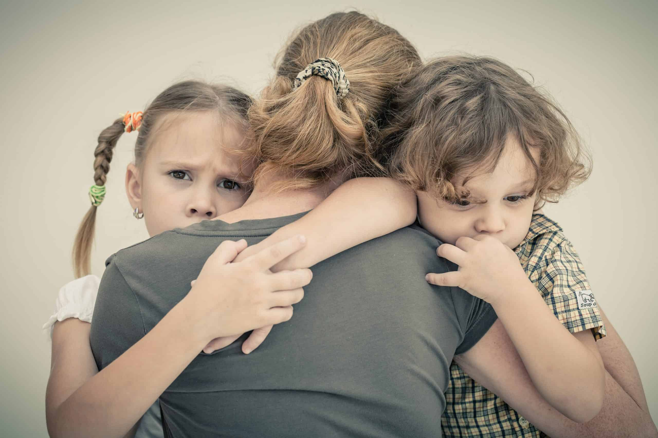 two sad children hugging their mother