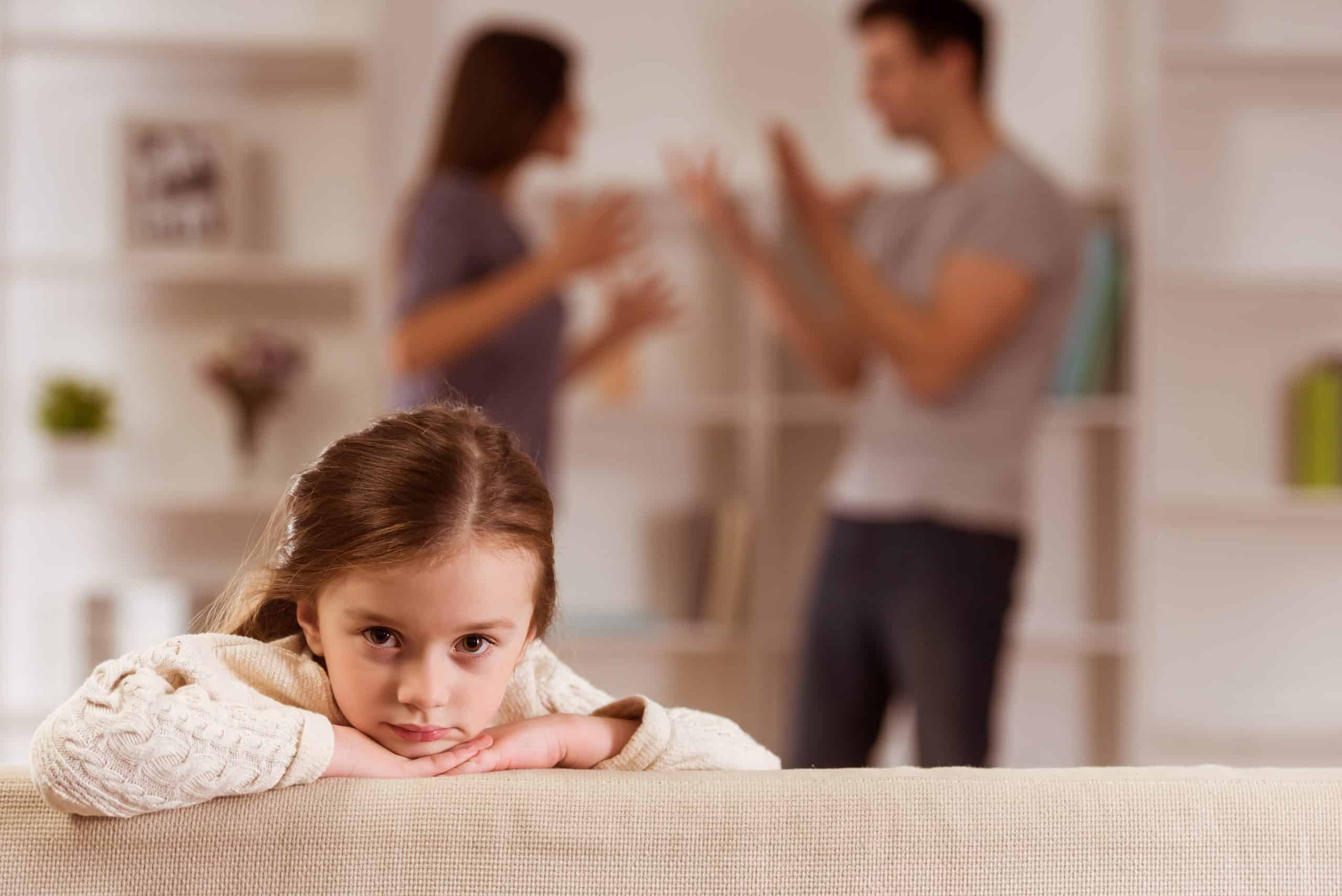 Little girl looking over the back of the couch with parents fighting in the background blurred