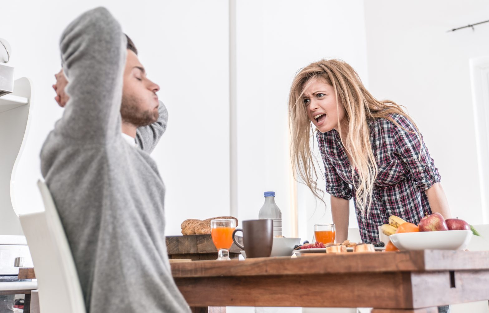 Couple fighting across the table over breakfast. Woman screaming at a man and the man has his hands on his head.
