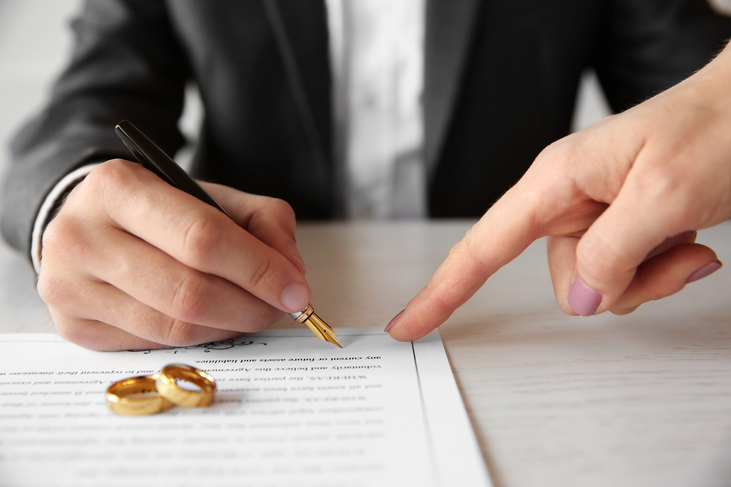 Man signing a document with wedding rings on the contract