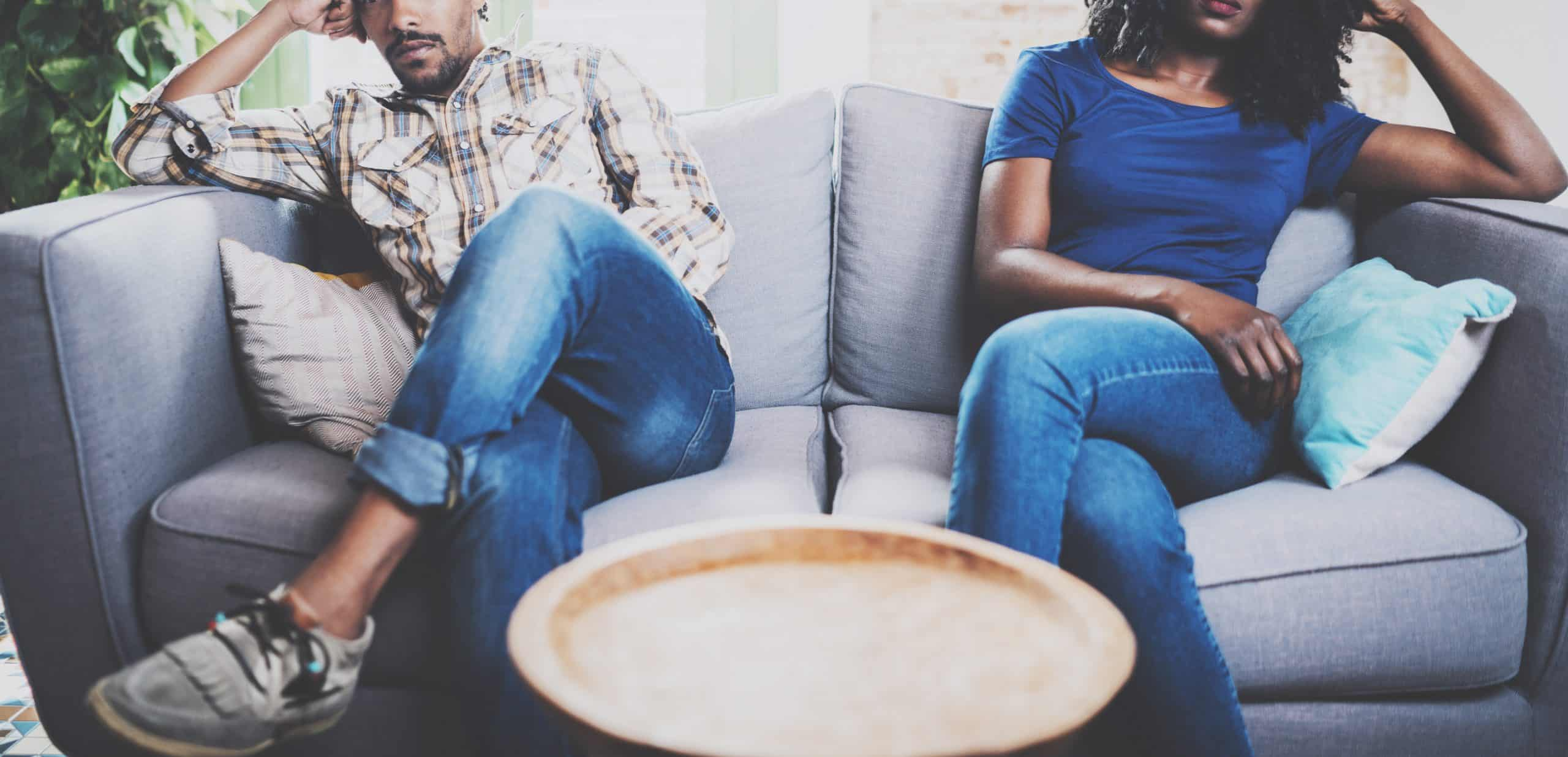 Young displeased black couple. American African men arguing with his stylish girlfriend, who is sitting on the couch next to him with legs crossed. Man looking away