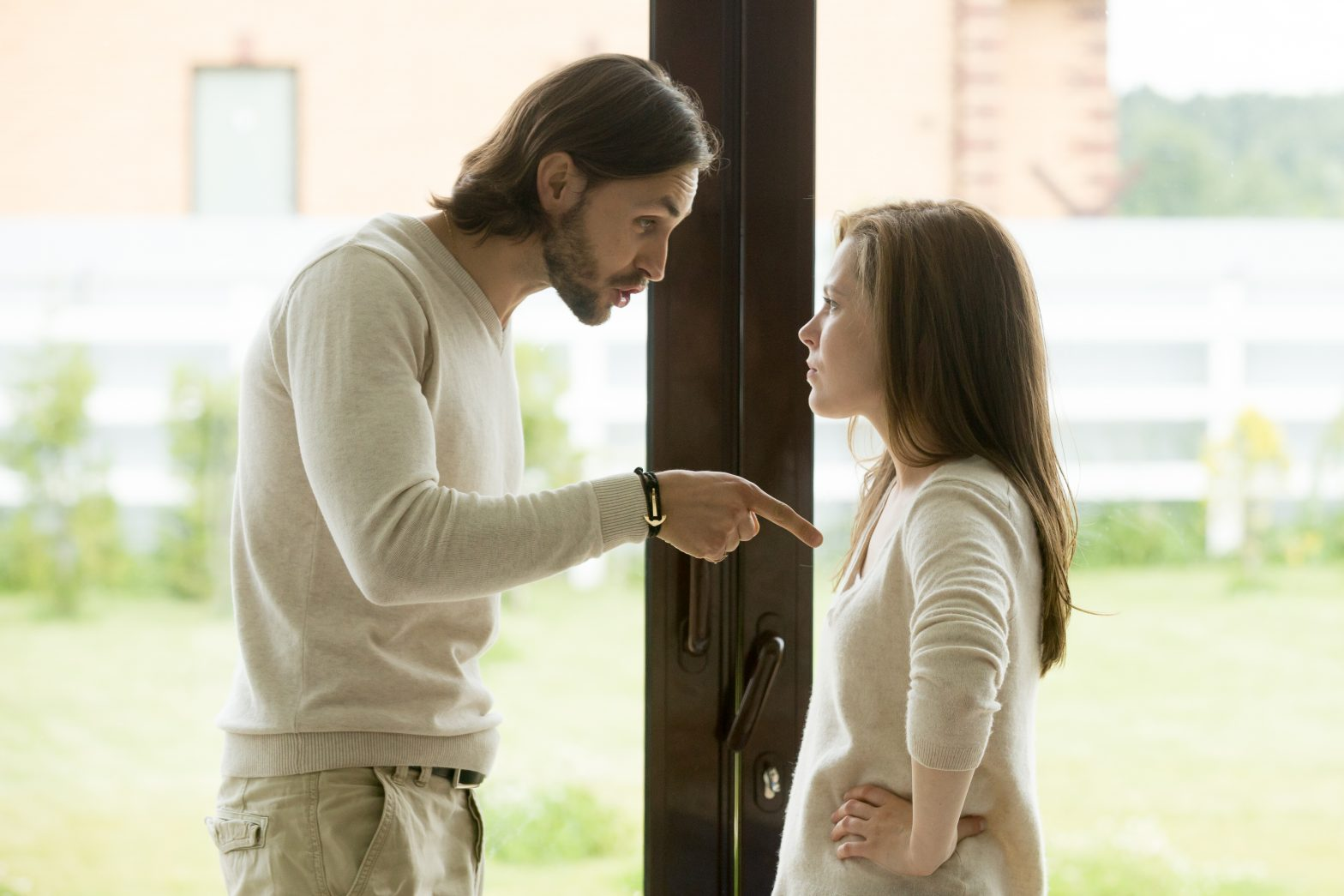 Unhappy young couple arguing standing at house door, angry husband pointing at wife with her hands on her hips
